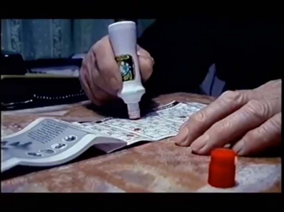 A man using a Gekkur card, which is similar to a bingo card