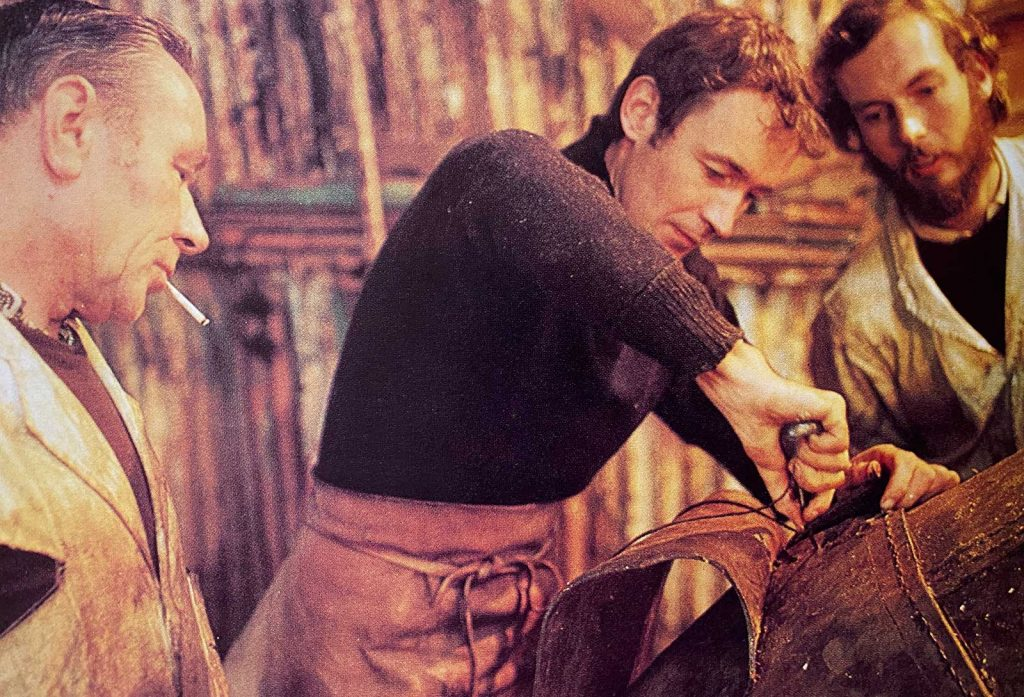 Tim Severin working on the leather hull of Brendan as master harness maker John O'Connell looks on.