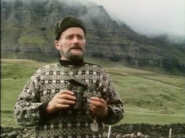A Faroese man in a patterned sweater holding binoculars