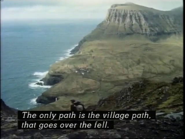 Postal carrier descending a mountain into the village of Gásadalur with subtitle captain saying: The only path is the village path that goes over the Fell.