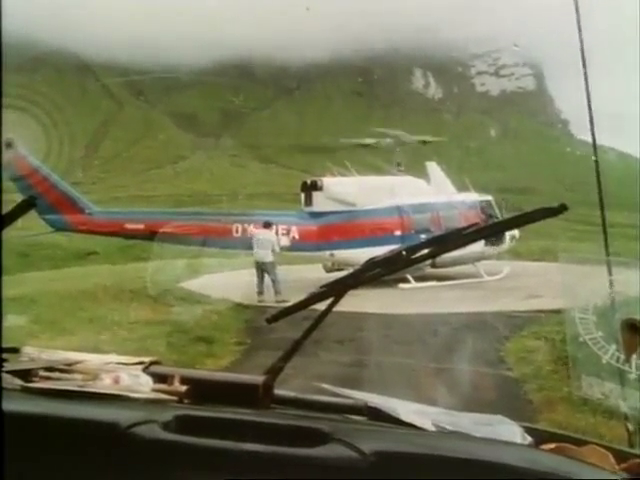 A helicopter seen through the windshield of a van.