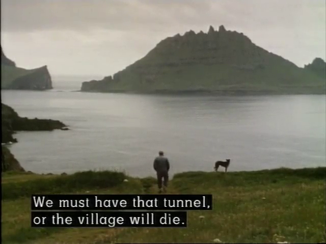 A man looks out over the ocean with the caption: we must have that tunnel, or the village will die.