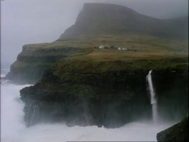 A waterfall off an ocean cliff during a storm.